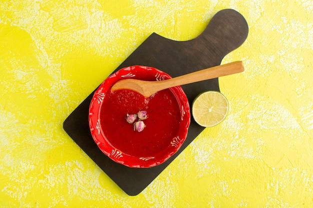 トップビュー黄色のテーブルにレモンとおいしいトマトスープ、スープミール野菜料理 無料写真