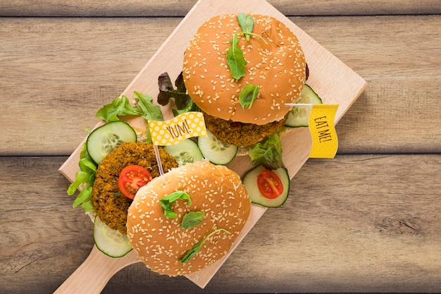 Top view delicious vegan burgers on wooden board Free Photo