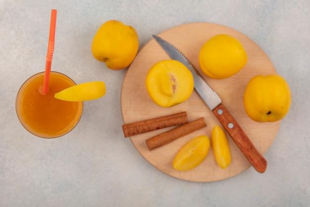 Vista dall'alto di deliziose pesche gialle su una tavola da cucina in legno con bastoncini di cannella con coltello con succo di pesca fresco su un bicchiere su sfondo bianco Foto Gratuite