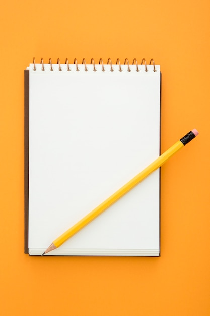 Top view desk arrangement with empty notepad on orange background Free Photo