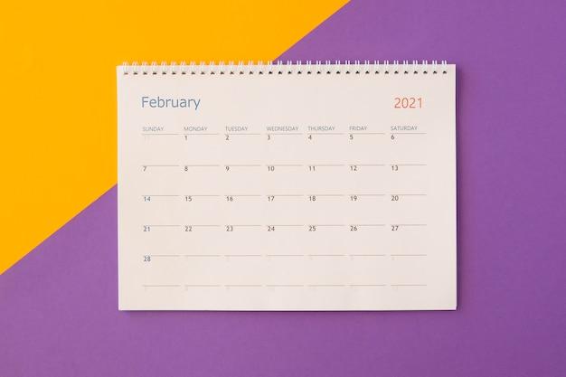 Calendario da tavolo vista dall'alto su sfondo colorato a contrasto Foto Gratuite