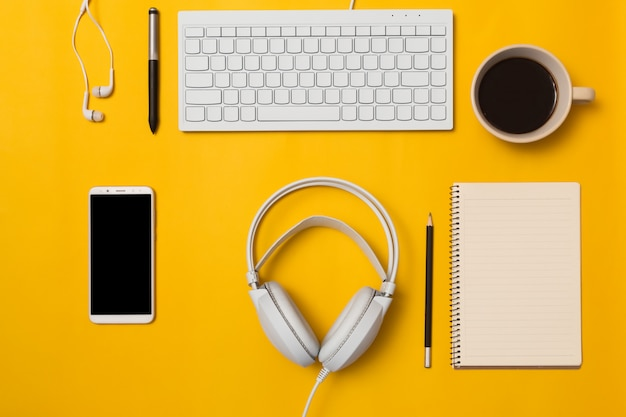 Top view of the desk and lifestyle on the color background. Premium Photo