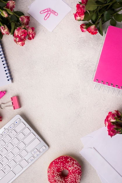 Top view of desk with keyboard and bouquet of roses Free Photo