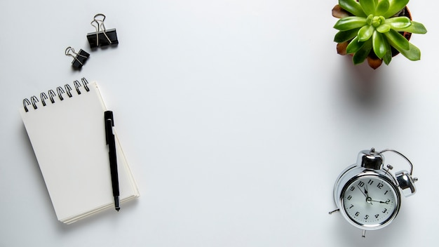 Top view desk with notepad and clock Free Photo