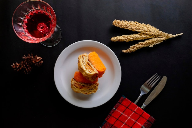 Топ вид десерт оранжевый круассаны торт со столом, стекло, вилка, нож на черном столе Premium Фотографии