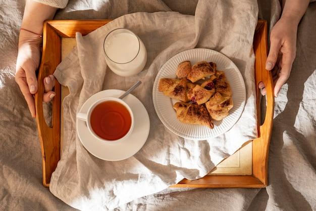 Vista dall'alto di dessert sul vassoio con tè e latte Foto Gratuite