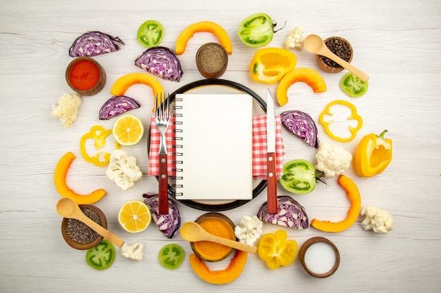 Vista dall'alto dieta scritta sul blocco note forchetta e coltello sulla piastra rotonda tagliare le verdure diverse spezie in ciotole sulla tavola di legno Foto Gratuite