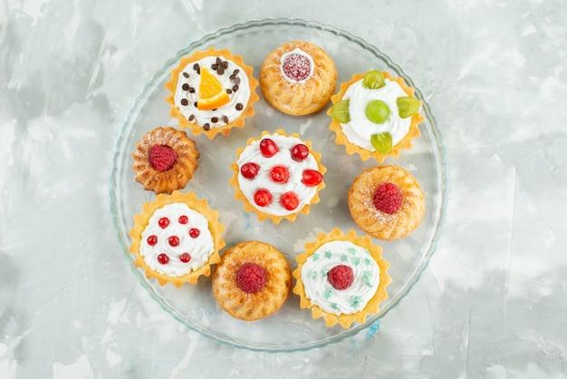 上面の光の表面にクリームとフレッシュフルーツの異なるケーキクッキー砂糖甘い 無料写真