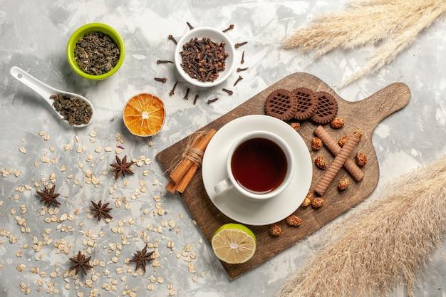 Вид сверху различных печений с чашкой чая на белой поверхности, сахарное печенье, конфеты, торт, сладкое, конфетное печенье Бесплатные Фотографии