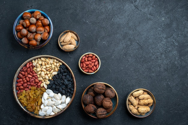 Top view different nuts composition of snacks on dark-grey background nuts snack photo walnut hazelnut Free Photo