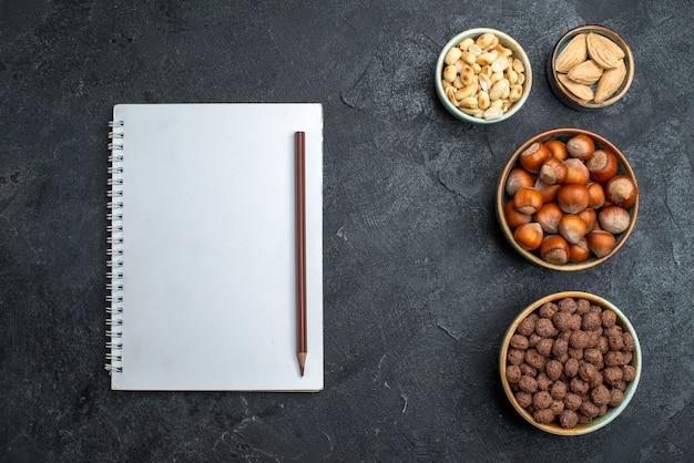 上面図灰色の背景にさまざまなナッツヘーゼルナッツとピーナッツナッツスナッククルミ食品植物 無料写真