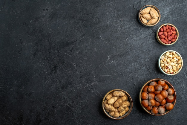 Top view different nuts hazelnuts and peanuts on grey background nut snack walnut food plant Free Photo