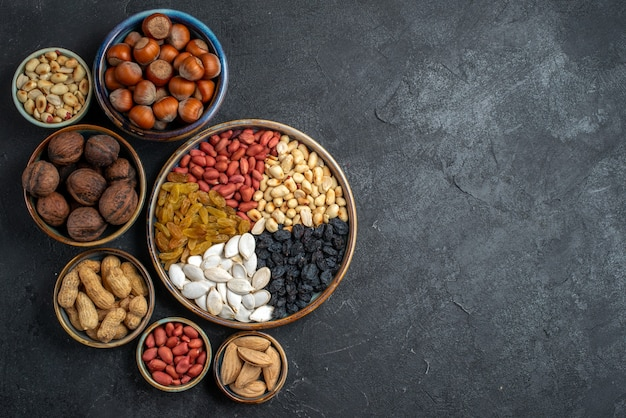 Top view different nuts with raisins and dried fruits on grey background nut snack raisin dry fruit nuts Free Photo