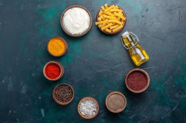 Вид сверху разные приправы с оливковым маслом и сырой итальянской пастой на темном столе Бесплатные Фотографии
