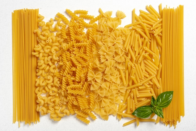 Top view of different types of pasta on plain background Free Photo