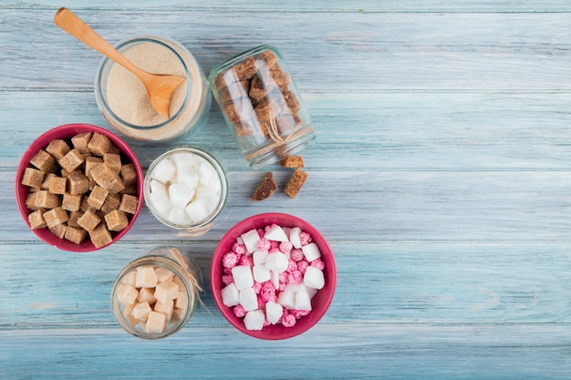 Top view of different types of sugar in glass jars on rustic background with copy space Free Photo