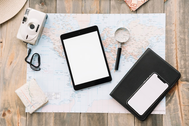 Top view of digital tablet; cell phone; magnifying glass and diary on map against wooden background Free Photo