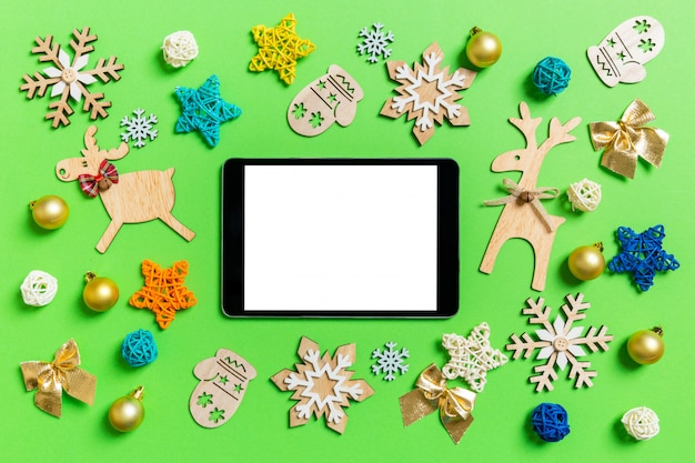 Top view of digital tablet on green with new year toys and decorations Premium Photo