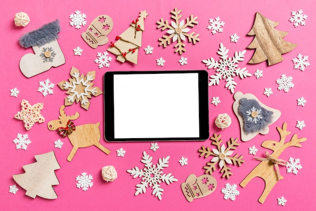 Top view of digital tablet on pink made of holiday decorations and toys. Premium Photo