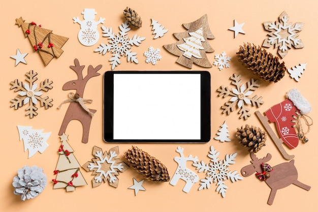 Top view of digital tablet surrounded with new year toys and decorations on orange. Premium Photo