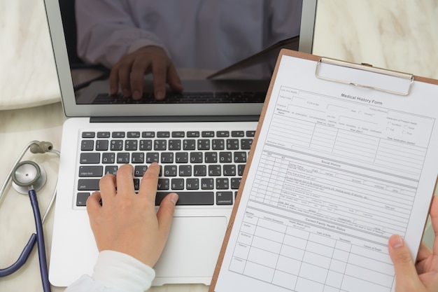 Top view of doctor using a laptop and a clipboard Free Photo