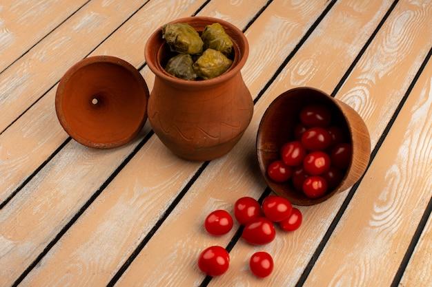 木製の机の上の茶色の鍋の中の赤いチェリートマトと一緒にトップビュードルマ 無料写真