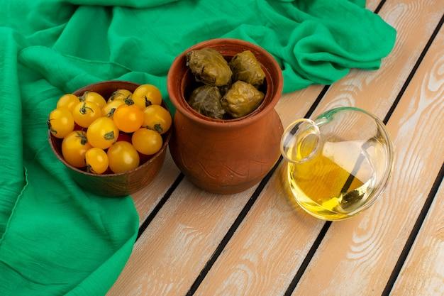Вид сверху долма вместе с желтыми помидорами и оливковым маслом на зеленой ткани и деревенском деревянном Бесплатные Фотографии