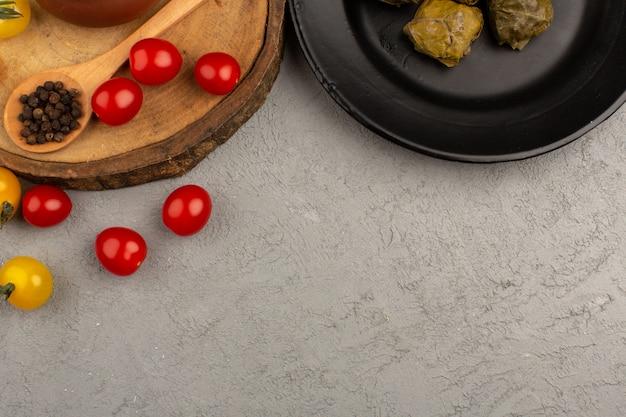 灰色の床に黒いプレート内のトマトとトップビュードルマ 無料写真