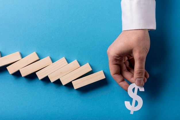 Top view of domino pieces and businessman holding dollar sign Premium Photo