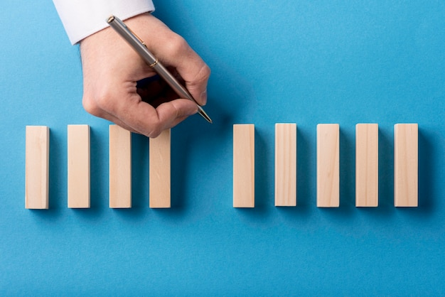 Top view of domino pieces and hand holding pen Premium Photo