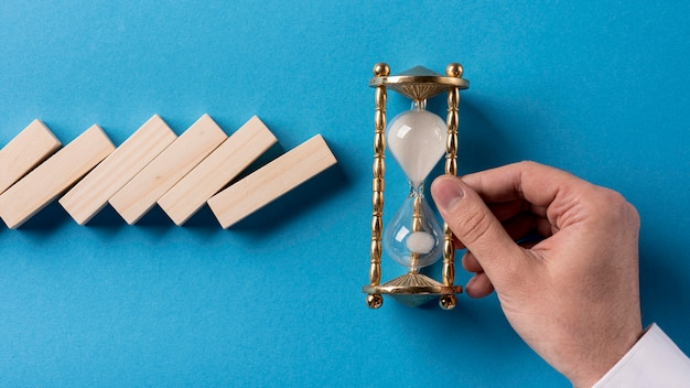 Top view of domino pieces with businessman holding hourglass Free Photo