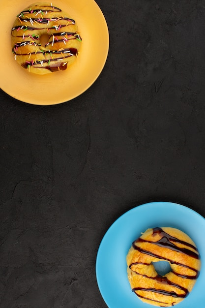 Top view donuts sweet yummy delicious inside colored plates on the dark background Free Photo