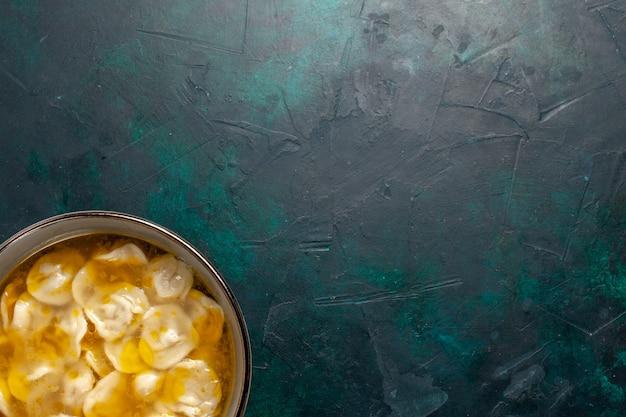 紺色の机の上の生地の中にひき肉が入った上面図の生地スープ材料スープ食品食事生地料理ディナーソース 無料写真