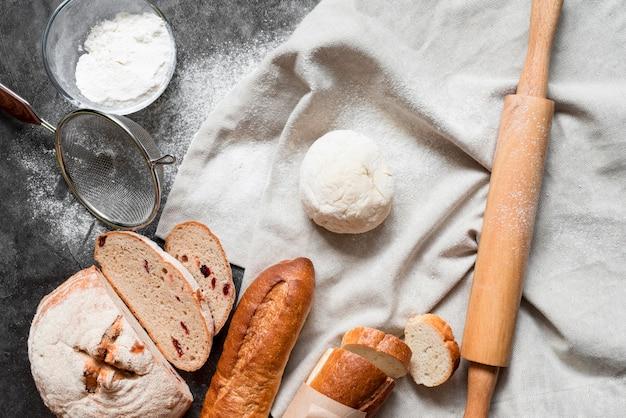 Вид сверху на тесто с хлебной смесью и скалкой Premium Фотографии