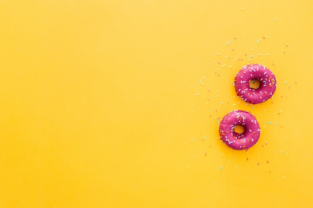 Top view of doughnut in pink icing on yellow background Free Photo