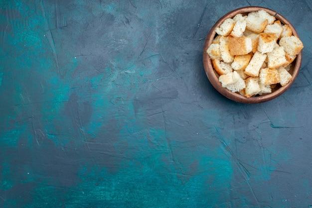 Vista dall'alto di fette biscottate di pane secco all'interno della ciotola marrone su fondente, fette biscottate di pane Foto Gratuite