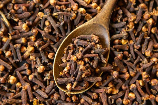Top view dried cloves with a wooden spoon Free Photo