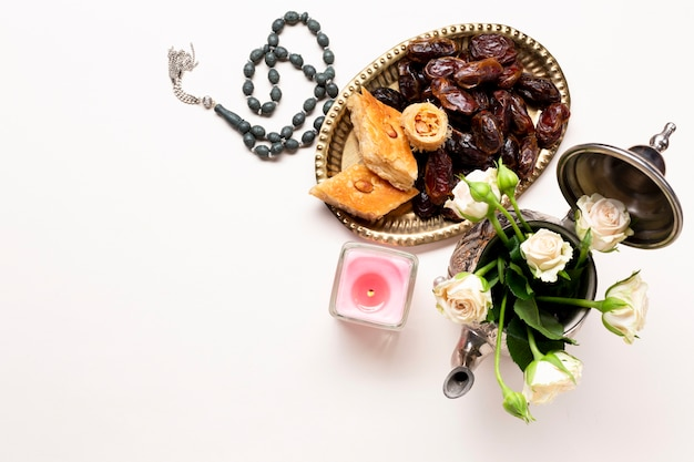 Top view dried dates with roses and candle Free Photo