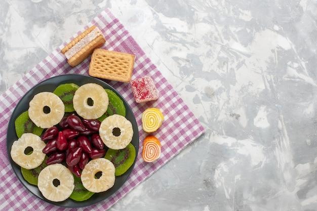 上面図ドライフルーツパイナップルリングハナミズキと白い背景のキウイスライスフルーツドライスイートシュガーサワー 無料写真