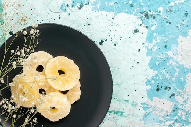 Vista dall'alto anelli di ananas essiccati all'interno della piastra su sfondo blu frutta ananas zucchero dolce secco Foto Gratuite