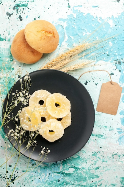 Top view dried pineapple rings inside plate on the blue surface cake bake fruit biscuit sweet sugar cookie Free Photo