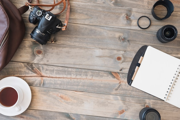 Top view of dslr camera; cup of tea; spiral notepad; pen; camera lens and bag on wooden table Free Photo