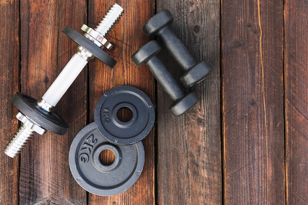 Top view of dumbbells and weight plates on wooden table Free Photo