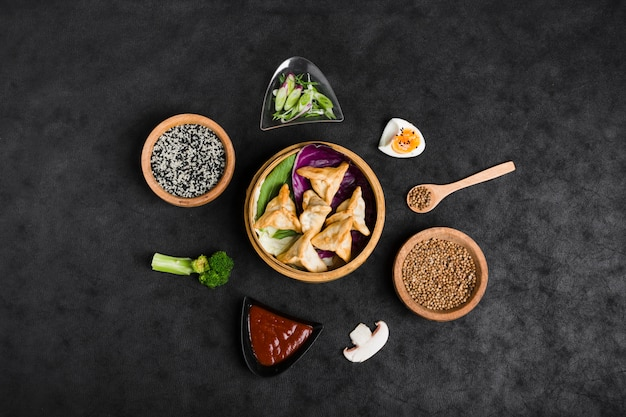 Top view of dumplings in steamers surrounded with sesame; sauce; coriander seeds; broccoli and mushroom on black background Free Photo