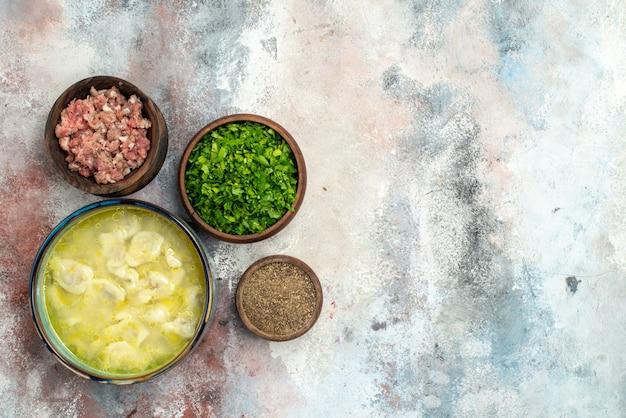 Vista dall'alto dushbara in una ciotola ciotole con verdure a base di carne pepe sulla superficie nuda spazio libero tradizionale piatto azerbaigiano Foto Gratuite