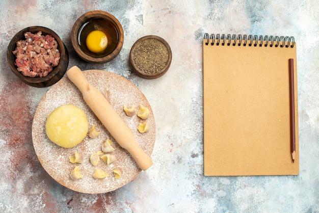 Вид сверху скалка для теста душбара на тестовой доске миски с мясом, перцем, яичным желтком, блокнотным карандашом, на обнаженной поверхности Бесплатные Фотографии