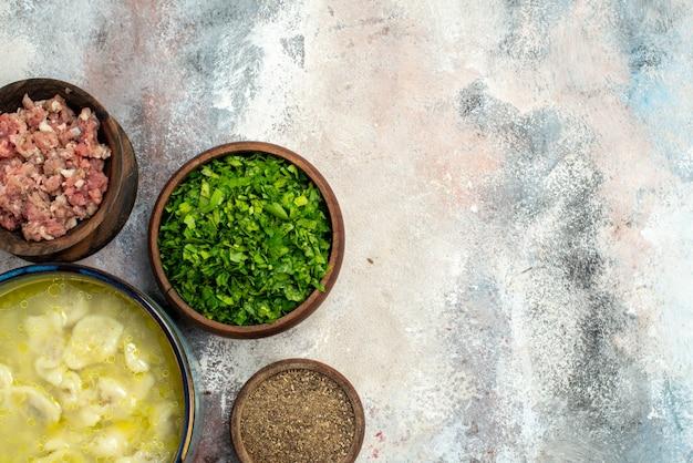 Vista dall'alto gnocchi di dushbara ciotole di zuppa con verdure di carne pepe sulla superficie nuda spazio libero piatto tradizionale azerbaigiano Foto Gratuite