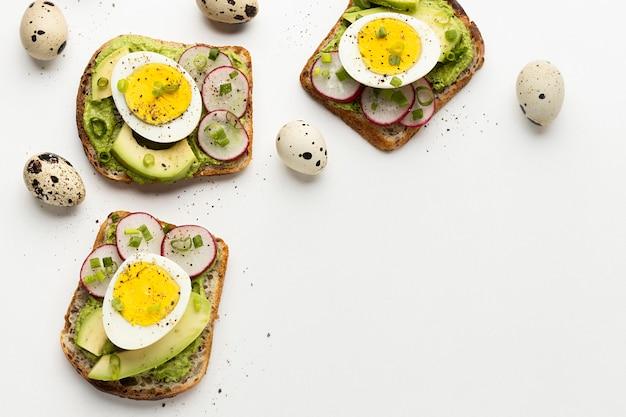 Vista dall'alto di panini con uova e avocado con spazio di copia Foto Gratuite