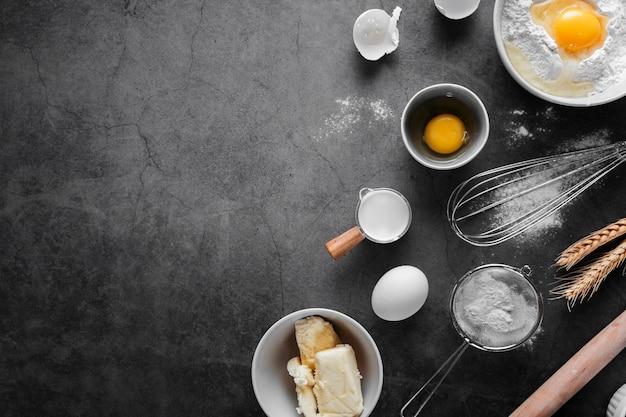 Вид сверху яйца с маслом и мукой на столе Premium Фотографии