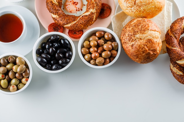Top view eggs with sausage in plate with a cup of tea, turkish bagel, olive, bread on white surface Free Photo